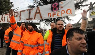 """Striking metro workers stand under a banner that reads: """"Strike 8th Day'' at the the central depot in Athens, Thursday, Jan. 24, 2013. Greece's conservative prime minister is holding emergency meeting after a deadline for striking public transport workers expired, leaving Athens' subway system closed for an eighth day. Strikers protesting pay cuts refused to return to work Thursday despite a court decision declaring their protest illegal. (AP Photo/Thanassis Stavrakis)"""