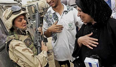 **FILE** An Iraqi woman greets U.S. Marine Sgt. Marykate Linnane in a Baghdad suburb on April 13, 2003. ( J.M. Eddins Jr./The Washington Times)