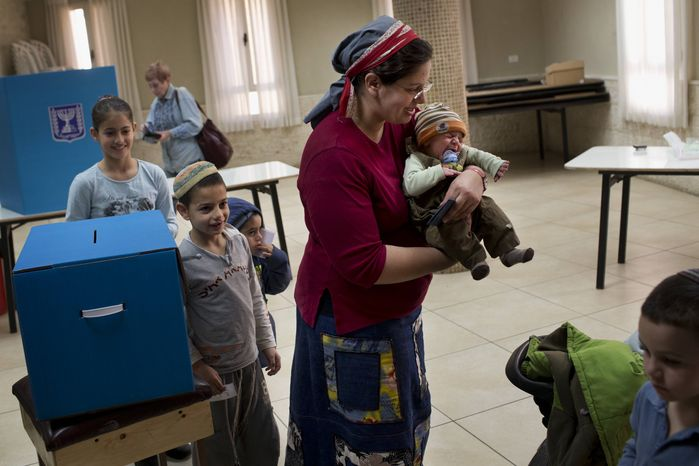 ** FILE ** An Israeli Jewish settler women leaves a polling station after casting her vote in the West Bank town of Hebron, Tuesday, Jan. 22, 2013. (AP Photo/Bernat Armangue)