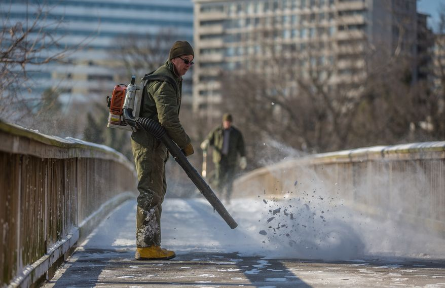 National Park Service rangers use high-powered leaf blowers to remove fresh snow from the walking bridge leading to Theodore Roosevelt island, in Washington, D.C., Thursday, Jan. 24, 2013.(Andrew S. Geraci/The Washington Times)