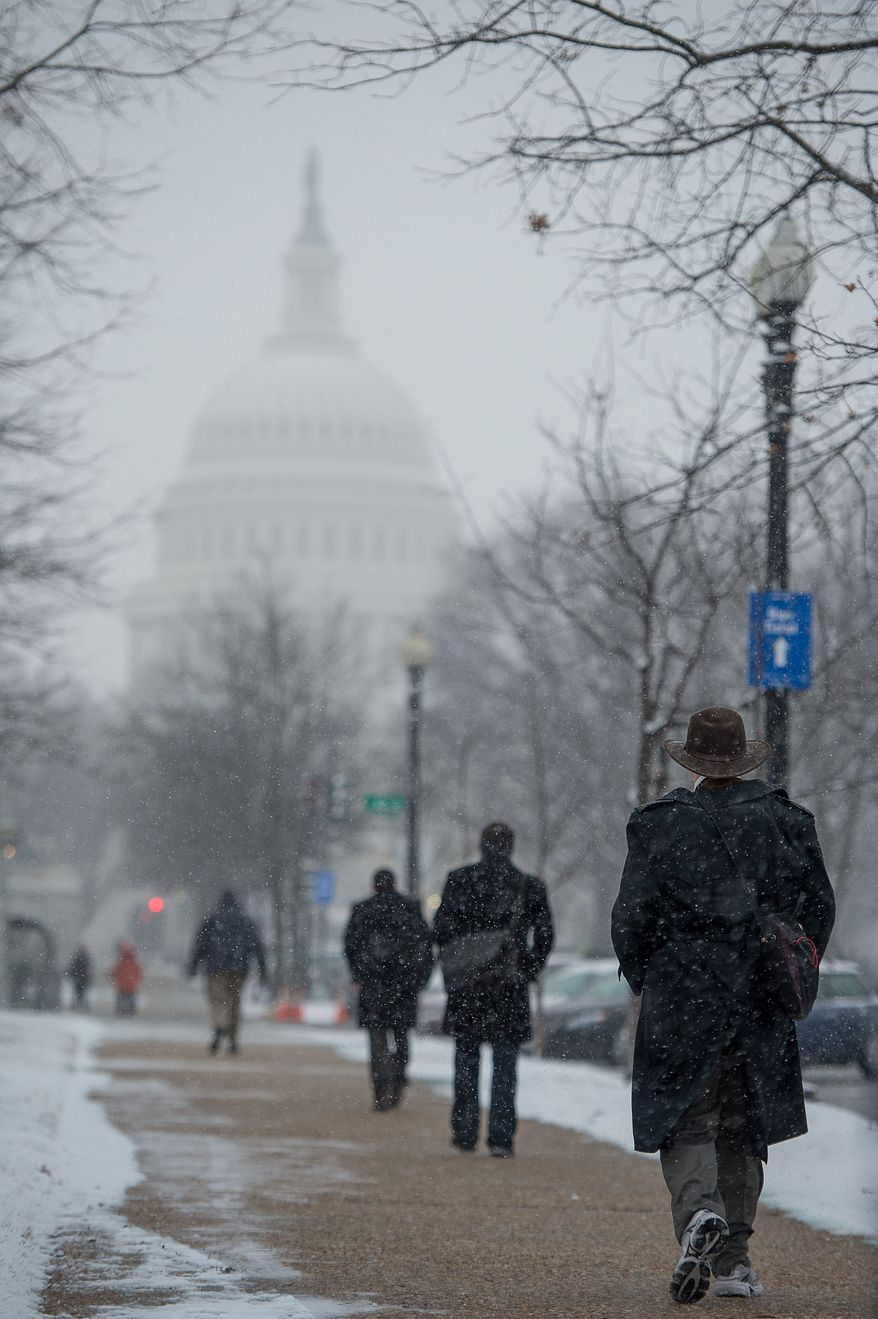 Light snow falls during morning rush hour as workers make their way to work on Capitol Hill, Washington, D.C., Thursday, Jan. 24, 2013. (Andrew Harnik/The Washington Times)