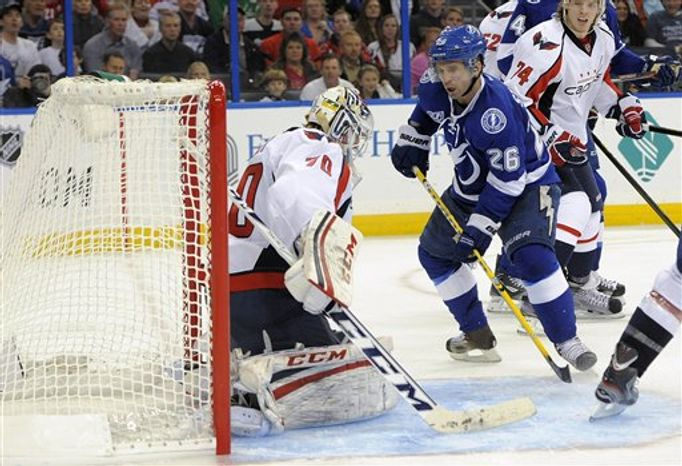 Tampa Bay Lightning right wing Martin St. Louis (26) scores a goal on Washington Capitals goalie Braden Holtby (70) during the second period of an NHL hockey game Saturday, Jan. 19, 2013, in Tampa, Fla. (AP Photo/Brian Blanco)