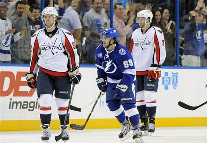 Tampa Bay Lightning left wing Cory Conacher, center, skates between Washington Capitals defensemen Mike Green, left, and Tom Poti after his goal during the third period of an NHL hockey game Saturday, Jan. 19, 2013, in Tampa, Fla. The Lightning won 6-3. (AP Photo/Brian Blanco)