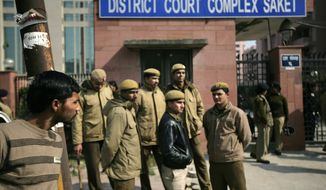 Delhi policemen stand guard Jan. 24, 2013, near the gate of a district court in New Delhi, where the trial of the five men charged accused in the gang rape and murder of a 23-year-old student began in a closed courtroom. (Associated Press)