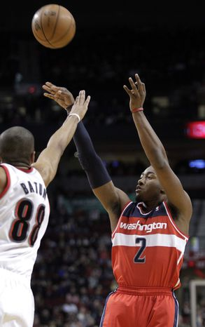 ** FILE ** Washington Wizards guard John Wall, right, shoots against Portland Trail Blazers forward Nicolas Batum during the first quarter of an NBA basketball game in Portland, Ore., Monday, Jan. 21, 2013. (AP Photo/Don Ryan)