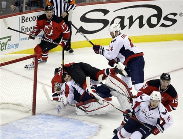 New Jersey Devils' Patrik Elias, of Czech Republic, crashes into Washington Capitals goalie Michal Neuvirth, bottom, of Czech Republic, during the second period of an NHL hockey game Friday, Jan. 25, 2013, in Newark, N.J. (AP Photo/Mel Evans)