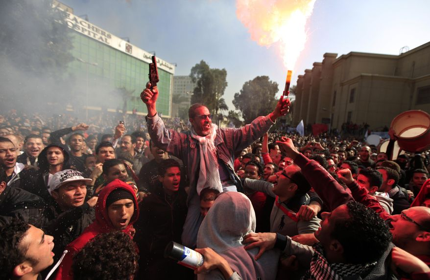 ** FILE ** Egyptian soccer fans of Al-Ahly club celebrate a court verdict that returned 21 death penalties in last years soccer violence, inside the club premises in Cairo, Egypt, Saturday, Jan. 26, 2013. (AP Photo/Khalil Hamra)