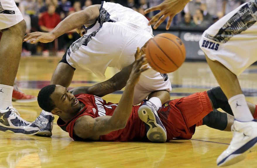 Georgetown guard Jabril Trawick (55) stands over Louisville guard Russ Smith (2) as Smith passes off a loose ball during the first half of an NCAA college basketball game, Saturday, Jan. 26, 2013, in Washington. (AP Photo/Alex Brandon)