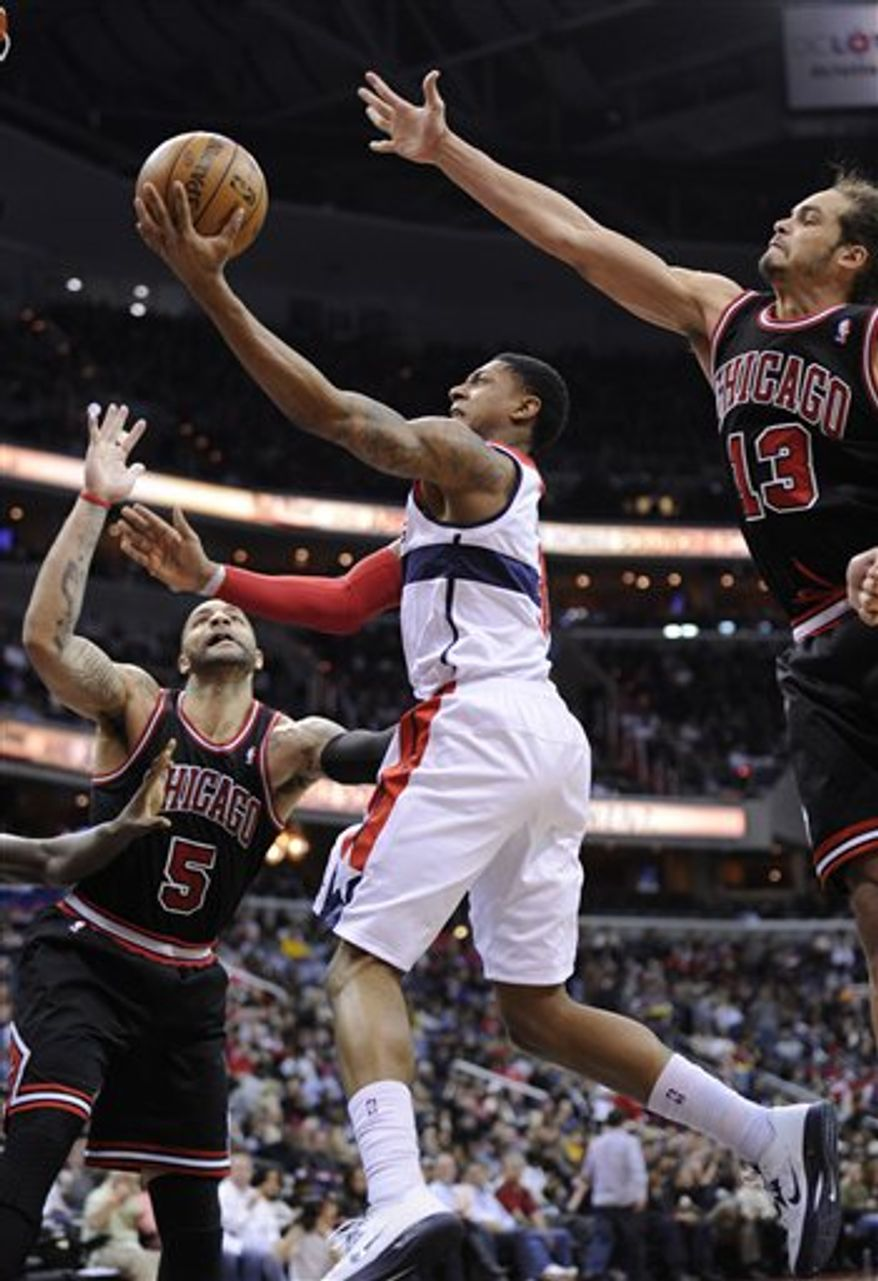 Washington Wizards guard Bradley Beal, center, goes to the basket against Chicago Bulls forward Carlos Boozer (5) and center Joakim Noah (13) during the second half of an NBA basketball game, Saturday, Jan. 26, 2013, in Washington. The Wizards won 86-73. (AP Photo/Nick Wass)