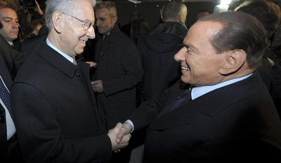 Italian Premier Mario Monti (left) and former Premier Silvio Berlusconi shake hands in Milan on Sunday, Jan. 27, 2013. (AP Photo/Antonio Calanni)