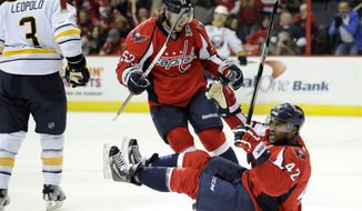 Washington Capitals right wing Joel Ward (42) celebrates his goal with teammate Mike Green (52) as Buffalo Sabres defenseman Jordan Leopold (3) looks on during the first period of an NHL hockey game on Sunday, Jan. 27, 2013, in Washington. (AP Photo/Nick Wass)