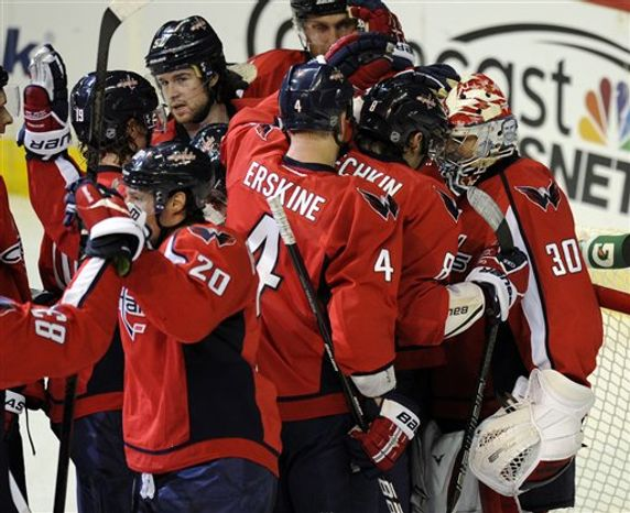 Washington Capitals goalie Michal Neuvirth (30), of the Czech Republic, celebrates the Capitals 3-2 win with Alex Ovechkin (8), of Russia, John Erskine (4) and others in an NHL hockey game against the Buffalo Sabres, Sunday, Jan. 27, 2013, in Washington. The Capitals won 3-2. (AP Photo/Nick Wass)