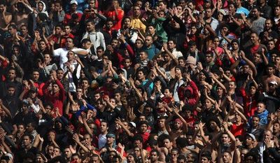 Fans of the Egyptian soccer club Al-Ahly celebrate in Cairo on Saturday, Jan. 26, 2013, after a court returned 21 death penalties in last year's soccer violence, which left 74 dead inside the club premises. (AP Photo/Khalil Hamra)