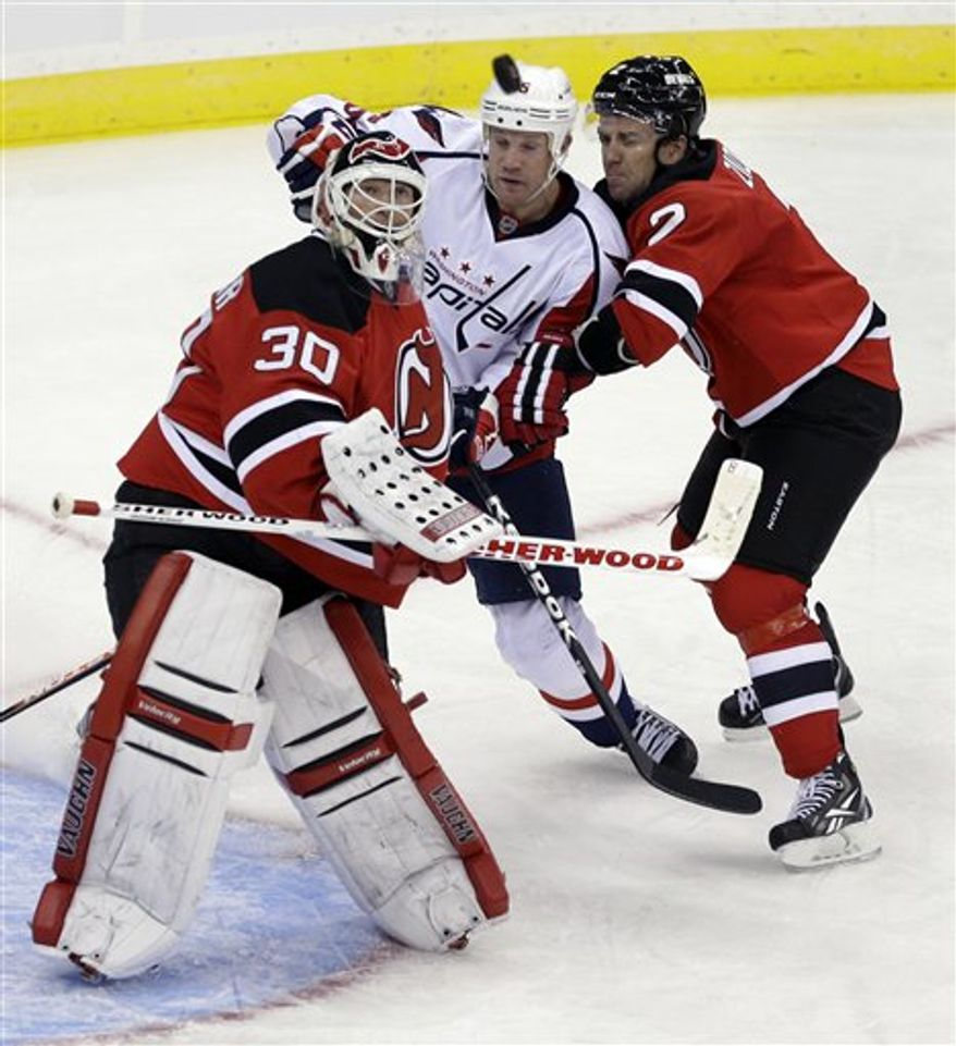 New Jersey Devils goalie Martin Brodeur (30) watches the puck as Washington Capitals' Jason Chimera (25) pushes close to the net with Devils' Marek Zidlicky, of the Czech Republic (2) during the third period of an NHL hockey game Friday, Jan. 25, 2013, in Newark, N.J. The Devils won 3-2. (AP Photo/Mel Evans)