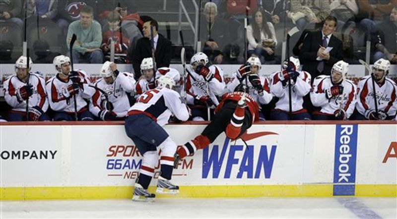 New Jersey Devils' Jacob Josefson, right, of Sweden, is knocked into the Washington Capitals bench by Capitals' Jason Chimera (25) during the second period of an NHL hockey game Friday, Jan. 25, 2013, in Newark, N.J. Devils won 3-2 in overtime. (AP Photo/Mel Evans)