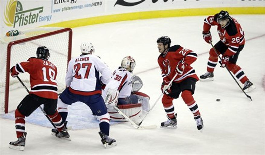 New Jersey Devils' Patrik Elias, right, of Czech Republic, scores a goal past Washington Capitals goalie Michal Neuvirth, bottom, of Czech Republic, during the second period of an NHL hockey game Friday, Jan. 25, 2013, in Newark, N.J. (AP Photo/Mel Evans)