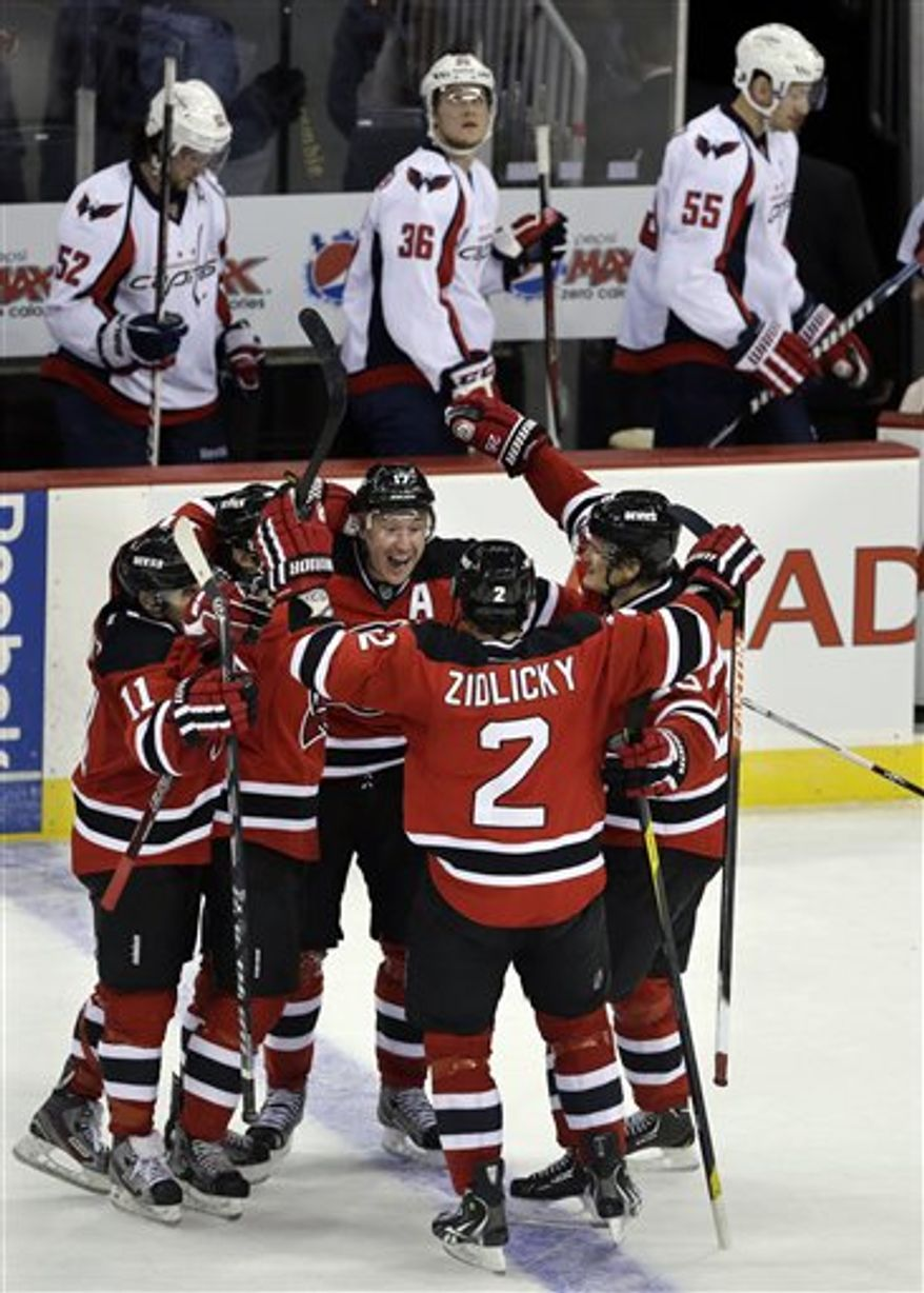 New Jersey Devils' Ilya Kovalchuk, center, of Russia, celebrates his game winning goal in overtime of an NHL hockey game against the Washington Capitals Friday, Jan. 25, 2013, in Newark, N.J. The Devils won 3-2. (AP Photo/Mel Evans)