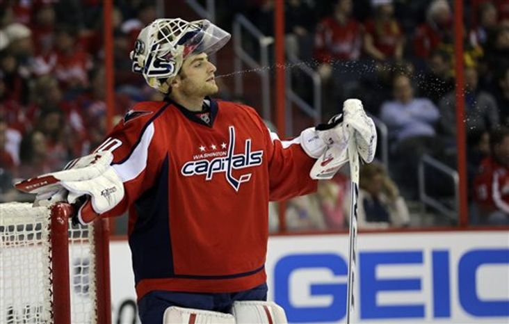 Washington Capitals goalie Braden Holtby (70) spits water during a timeout in the third period of an NHL hockey game against the Winnipeg Jets Tuesday, Jan. 22, 2013 in Washington. The Jets won 4-2. (AP Photo/Alex Brandon)