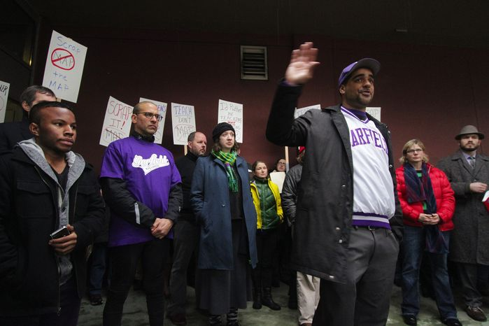 Garfield High School social studies teacher Jesse Hagopian (with his hand raised) and other Seattle teachers are refusing to administer to their students a standardized test they say is flawed. (Seattle Times via Associated Press)