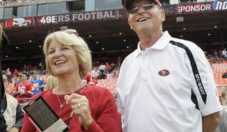 Jackie (left) and Jack Harbaugh, parents of San Francisco 49ers coach Jim Harbaugh and Baltimore Ravens coach John Harbaugh, stand before an NFL football game between the 49ers and the Seattle Seahawks in San Francisco in 2011. (AP Photo/Paul Sakuma)