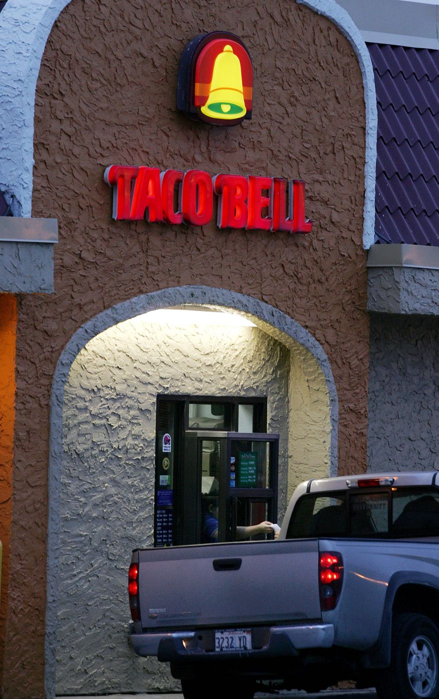 **FILE** A worker hands an order from the drive-thru window at a Taco Bell restaurant in South Plainfield, N.J., on Dec. 12, 2006. (Associated Press)
