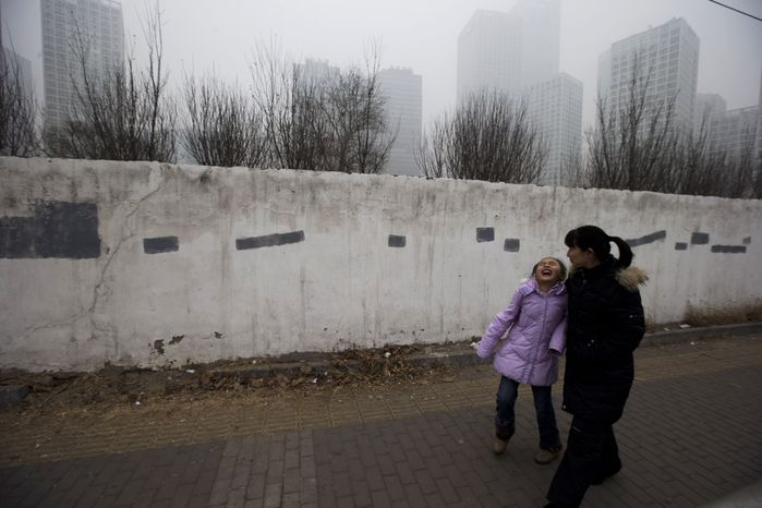 A child laughs as she passes by a smog-shrouded residential district in Beijing on Jan. 29, 2013. Extremely high pollution levels shrouded eastern China for the second time in about two weeks, forcing airlines in Beijing and elsewhere to cancel flights because of poor visibility and prompting government warnings for residents to stay indoors. (Associated Press)