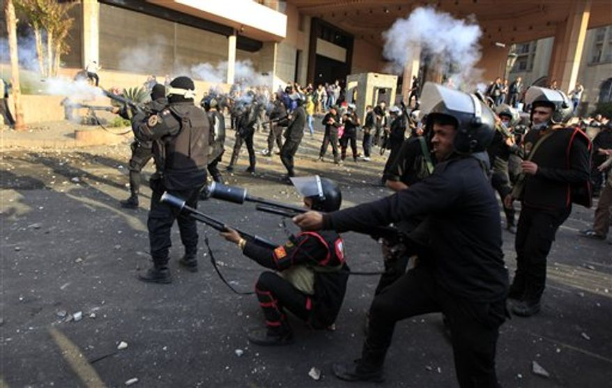 Egyptian riot police fire tear gas at protesters, not seen, during clashes in front of the Semiramis Intercontinental hotel, background near Tahrir Square, Cairo, Egypt,Tuesday, Jan. 29, 2013. (AP Photo/Khalil Hamra)