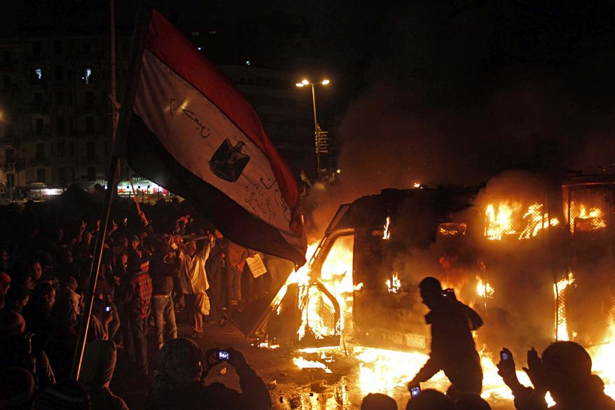 "In this Monday, Jan. 28, 2013, photo, Egyptian protesters use camera phones to capture a burning state security armored vehicle that demonstrators commandeered during clashes with security forces nearby and brought to Tahrir Square and set it alight, in Cairo, Egypt. On Tuesday, Jan. 29, 2013. Egypt's army chief warns of ""the collapse of the state"" if political crisis continues. (AP Photo/Mostafa El Shemy)"