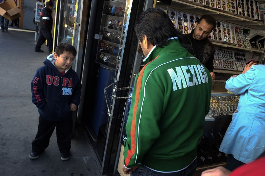 Mexican immigrant Roberto Garcia (center) and son Alan (left) look at wristwatches while shopping in Los Angeles on Jan. 28, 2013. (Associated Press)