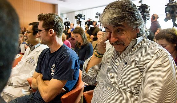 Alex Marrocco, right, the father of Iraq war veteran Brendan Marrocco appears to get emotional as his son speaks at a press conference after a surgical team lead by Johns Hopkins physicians successfully performed the hospitalís first bilateral arm transplant on him, Baltimore, Md., Tuesday, January 29, 2013. Marrocco, who lost all four limbs from a bomb outside Baghdad, Iraq., is expected to slowly develop control over his new arms over the next year and a half. (Andrew Harnik/The Washington Times)
