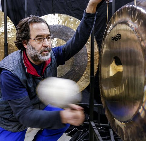 Andrew Borakove of Gongs Unlimited strikes a gong in his warehouse in Lincoln, Neb. The former comedy writer from California counts Roger Daltry of The Who among his customers. (Associated Press)