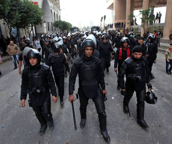 associated press  Egyptian riot police gird for clashes with protesters in Cairo on Wednesday. Political violence has left more than 60 dead in the past week, and the head of the armed forces warned of the potential for political chaos.