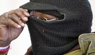 **FILE** Darryl Sey pulls his ski mask up higher as he waits in freezing temperatures for a bus to take him home on Jan. 7, 2010 in Nashville, Tenn. (Associated Press)