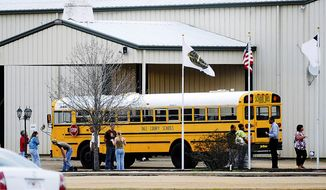 In this Tuesday, Jan 29, 2013, photo, residents look over the school bus where a shooting occurred near Destiny Church along U.S. 231, just north of Midland City, Ala. (AP Photo/The Dothan Eagle, Danny Tindell)
