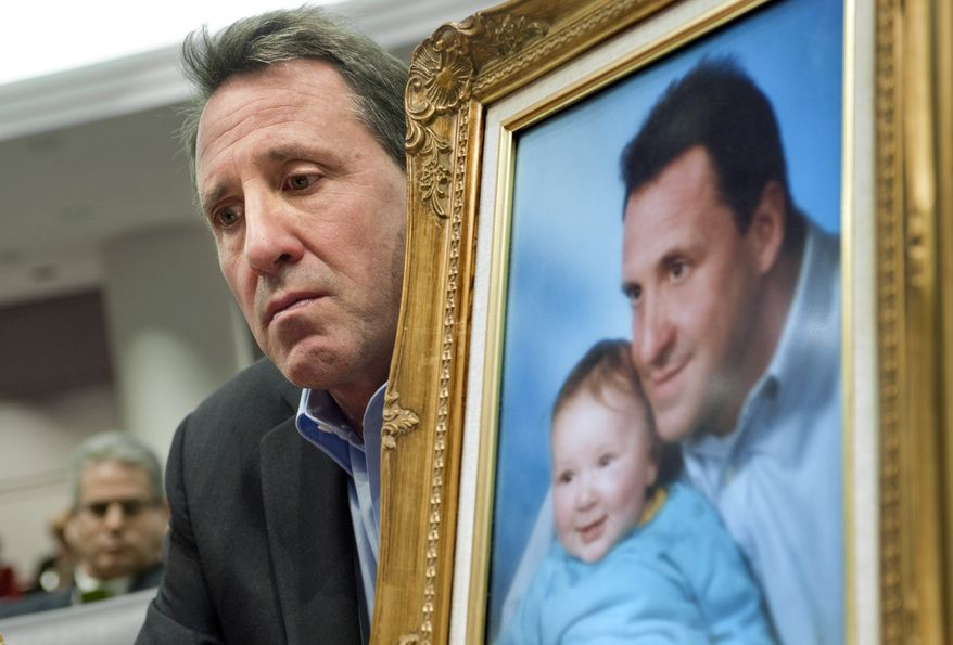 ** FILE ** Neil Heslin, holding a picture of himself with son Jesse, testifies before a legislative subcommittee hearing on gun laws in Hartford, Conn., on Monday, Jan. 28, 2013. (AP Photo/Jessica Hill)