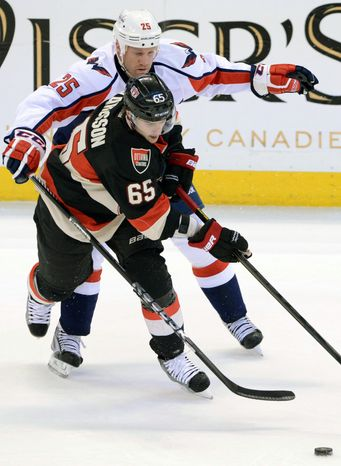 Ottawa Senators' Erik Karlsson (65) battles Washington Capitals' Jason Chimera for the puck during the first period of an NHL hockey game at the Scotia Bank Place in Ottawa, Ontario, on Tuesday, Jan. 29, 2013. (AP Photo/The Canadian Press, Sean Kilpatrick)
