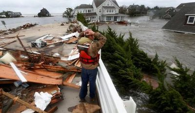 Brian Hajeski, 41, of Brick, N.J., reacts on Tuesday, Oct. 30, 2012, as he looks at the debris of a home that washed up onto the Mantoloking Bridge the morning after Superstorm Sandy rolled through Mantoloking, N.J. Sandy caused multiple fatalities, halted mass transit and cut power to more than 6 million homes and businesses. (AP Photo/Julio Cortez)