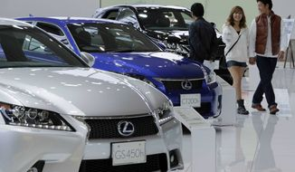 ** FILE ** A couple walk by Lexus models displayed at a Toyota Motor Corp. showroom in Tokyo on Monday, Nov. 5, 2012. (AP Photo/Koji Sasahara)