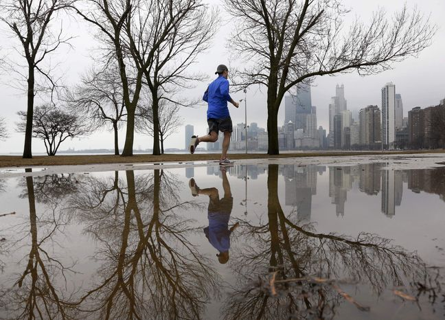 A lone jogger makes his way along Lake Michigan in unseasonably warm temperatures at Chicago's North Avenue Beach Tuesday, Jan. 29, 2013, in Chicago. Unseasonably warm temperatures broke records in the Chicago area with thunderstorm expected to usher in freezing temperatures and snow Wednesday. (AP Photo/Charles Rex Arbogast)