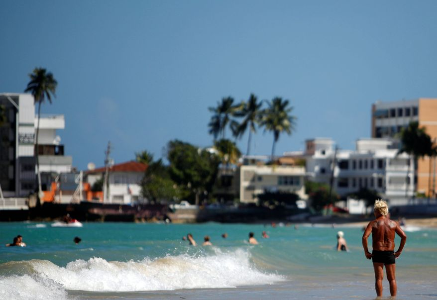 Visitors take in a sunny day and splash in the water at Isla Verde Beach, in Carolina, Puerto Rico. (Associated Press)