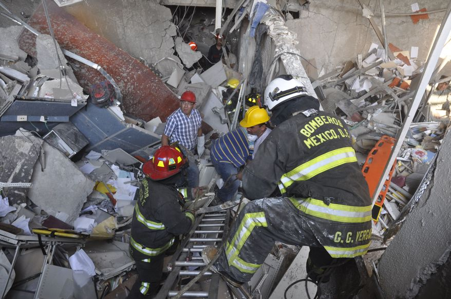 Firefighters belonging to the Tacubaya sector and workers dig for survivors after an explosion on Jan. 31, 2013, in Mexico City at an adjacent building to the executive tower of Mexico's state-owned oil company PEMEX. (Associated PRess)