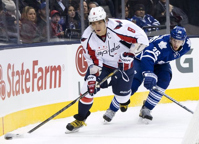 Washington Capital forward Alexander Ovechkin, left, skates by Toronto Maple Leafs defenseman Carl Gunnarsson during the first period of an NHL hockey game in Toronto on Thursday, Jan. 31, 2013. (AP Photo/The Canadian Press, Nathan Denette)