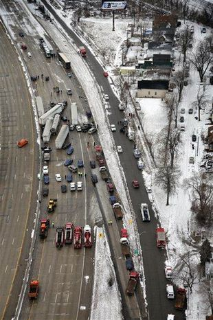 Emergency personnel respond at the scene of one of a mile-long series of crashes along Interstate 75 near the Springwells exit on the southwest side of Detroit Thursday, Jan. 31. At least three people are dead, including two children, and 20 more were injured in the pileups. (Associated Press)