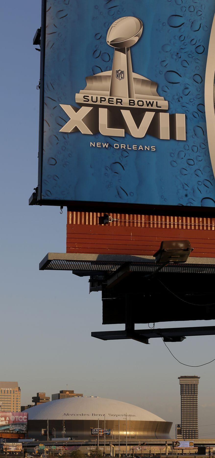 The Superdome is seen in the distance beyond a billboard Wednesday, Jan. 30, 2013, in New Orleans. The city will host the Super Bowl XLVII football game between the Baltimore Ravens and the San Francisco 49ers Sunday. (AP Photo/Charlie Riedel)