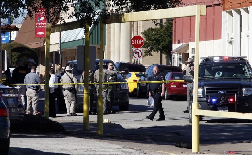 Law enforcement officers investigate the scene of a shooting in downtown Kaufman, Texas, on Jan. 31, 2013. A prosecutor was shot and killed near the Texas courthouse where he worked, and authorities said they were searching for two suspects. (Associated Press/The Dallas Morning News)