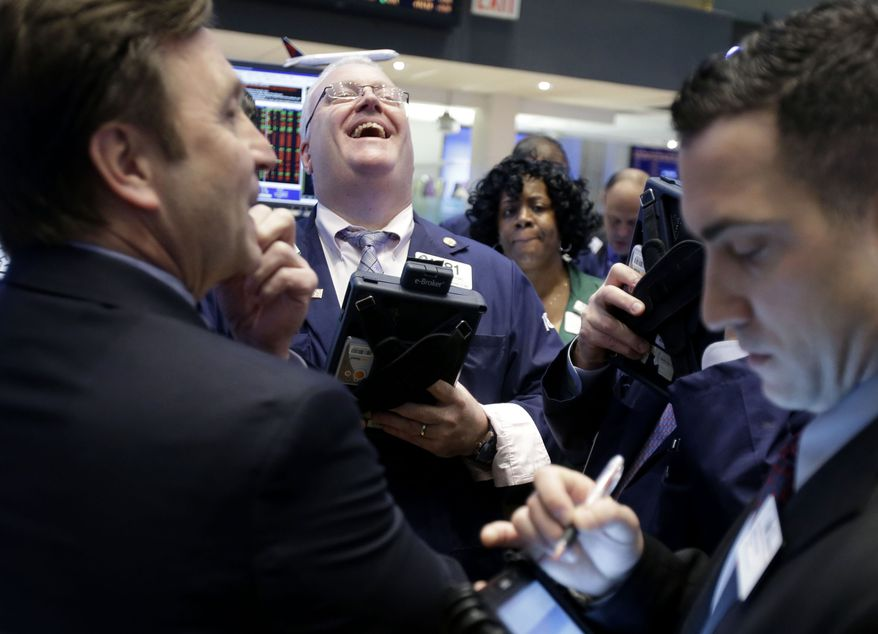 A trader laughs while working on the floor of the New York Stock Exchange in New York on Jan. 31, 2013. (Associated Press)