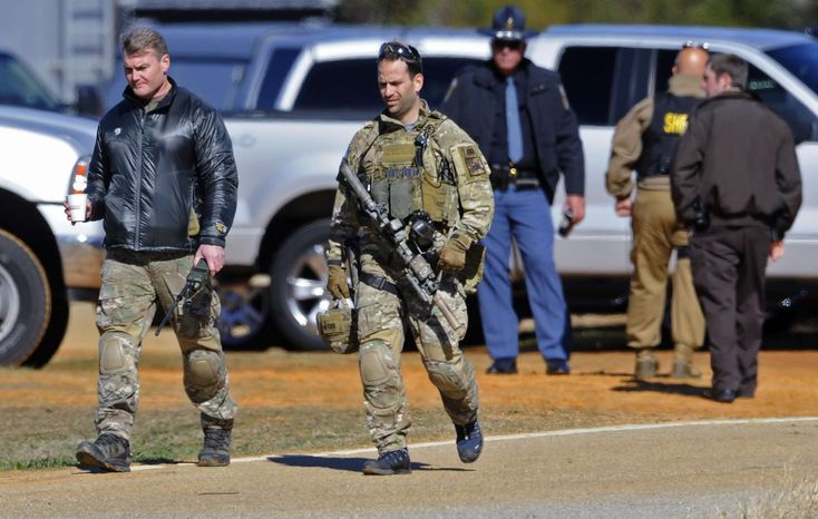 Law officers at the Dale County hostage scene in Midland City, Ala., on Thursday morning, Jan. 31, 2013. A gunman holed up in a bunker with a 5-year-old hostage has kept law officers at bay since the standoff began when he killed a school bus driver and dragged the boy away, authorities said. (AP Photo/Montgomery Advertiser, Mickey Welsh)