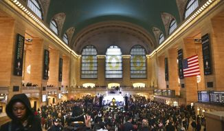 Crowds gather as Grand Central Terminal kicks off its centennial celebration on Friday, Feb. 1, 2013, in New York. New Yorkers are celebrating the 100th birthday of Grand Central terminal with music, speeches and a cake shaped like the main concourse's famous clock. (AP Photo/Bebeto Matthews)