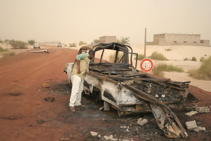 A man takes a close look at a burned-out truck in Timbuktu, Mali, on Jan. 31, 2013. Islamic militants fled from the area when French special forces parachuted in to liberate the city of Timbuktu several days ago. (Associated Press)