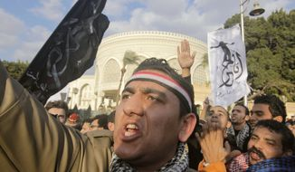 "Egyptians shout slogans during a demonstration against President Mohammed Morsi in front of the presidential palace in Cairo on Feb. 1, 2013. Arabic on the banner at right reads, ""I'm free.'"" (Associated Press)"